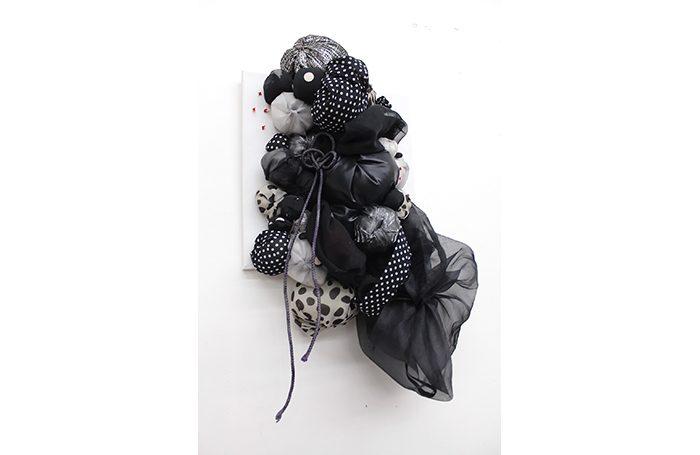 "009-09   Unfair   25""x15""x7""   Fabric, cotton, ribbon on canvas   $3,000.00"